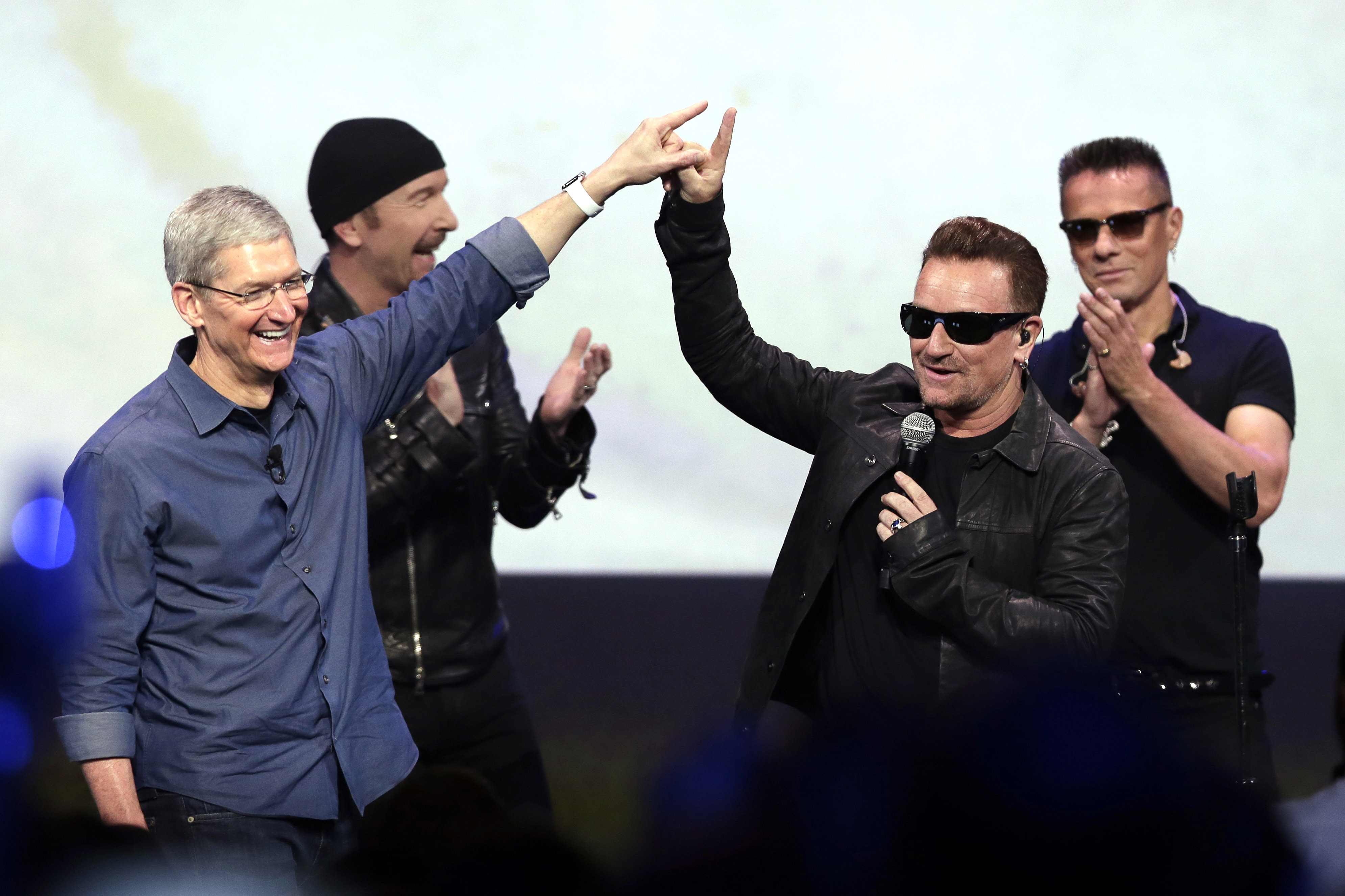 Apple CEO Tim Cook, left, greets Bono from the band U2 after they preformed at the end of the Apple event on Tuesday, Sept. 9, 2014, in Cupertino, Calif. Apple unveiled a new Apple Watch, the iPhone 6 and Apple Pay. (AP Photo/Marcio Jose Sanchez)