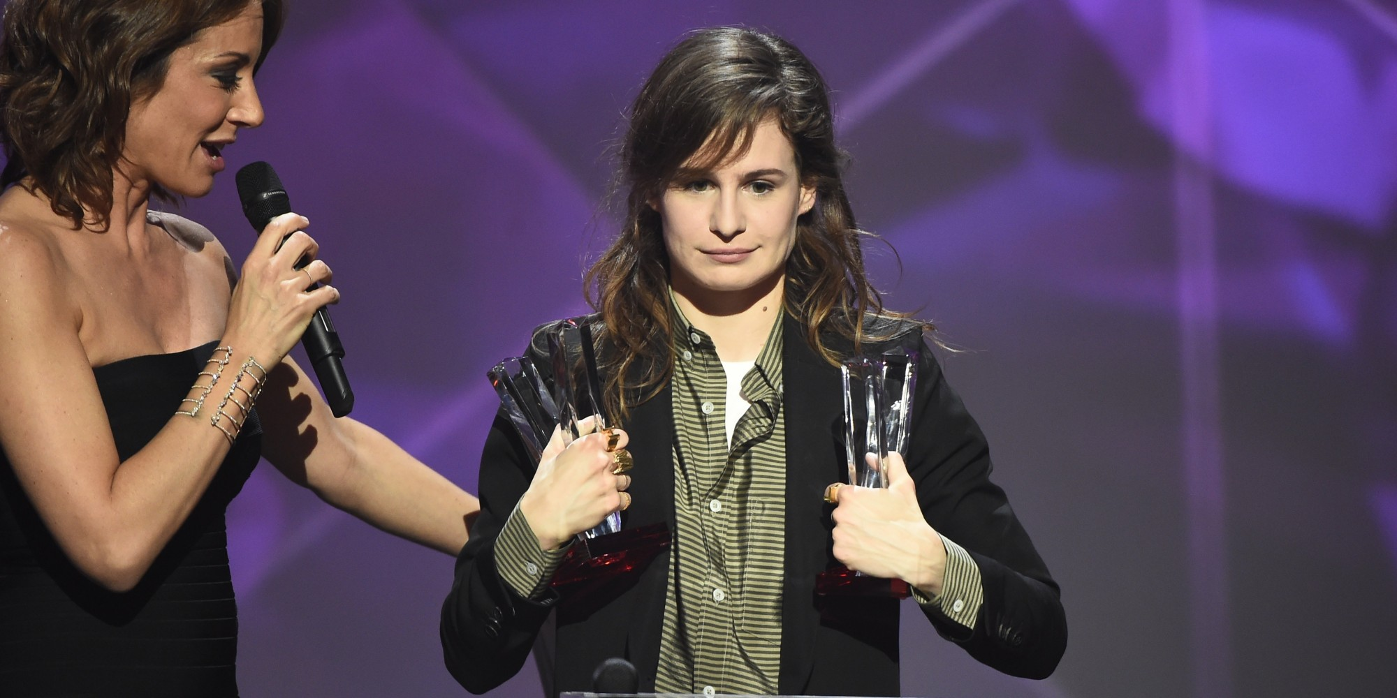 "French singer of the band ""Christine and the Queens"" Heloise Letissier (R), flanked by French TV host and Master of Ceremony Virginie Guilhaume (L), smiles as she received the best newcomer live show award and the best video clip award during the 31st Victoires de la Musique, the annual French music awards ceremony, on February 12, 2016 at the Zenith concert hall in Paris. AFP PHOTO / BERTRAND GUAY / AFP / BERTRAND GUAY"